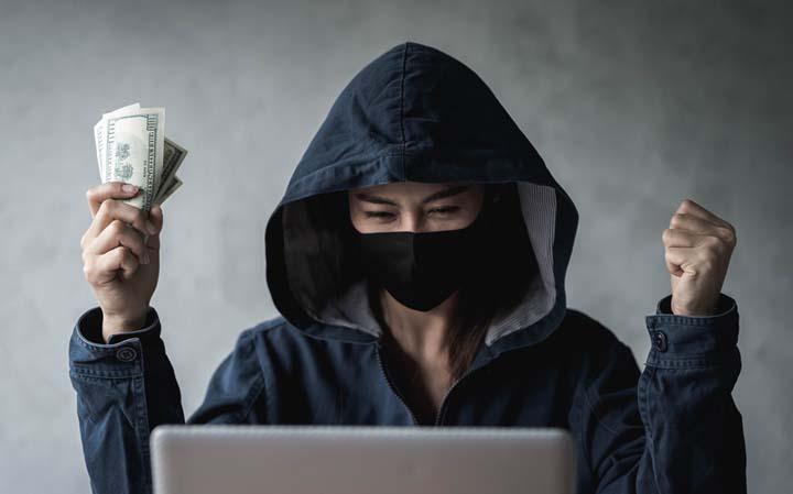 dangerous hooded hacker held the money after successfully hacking - ¿Que hacer en caso de cryptovirus?